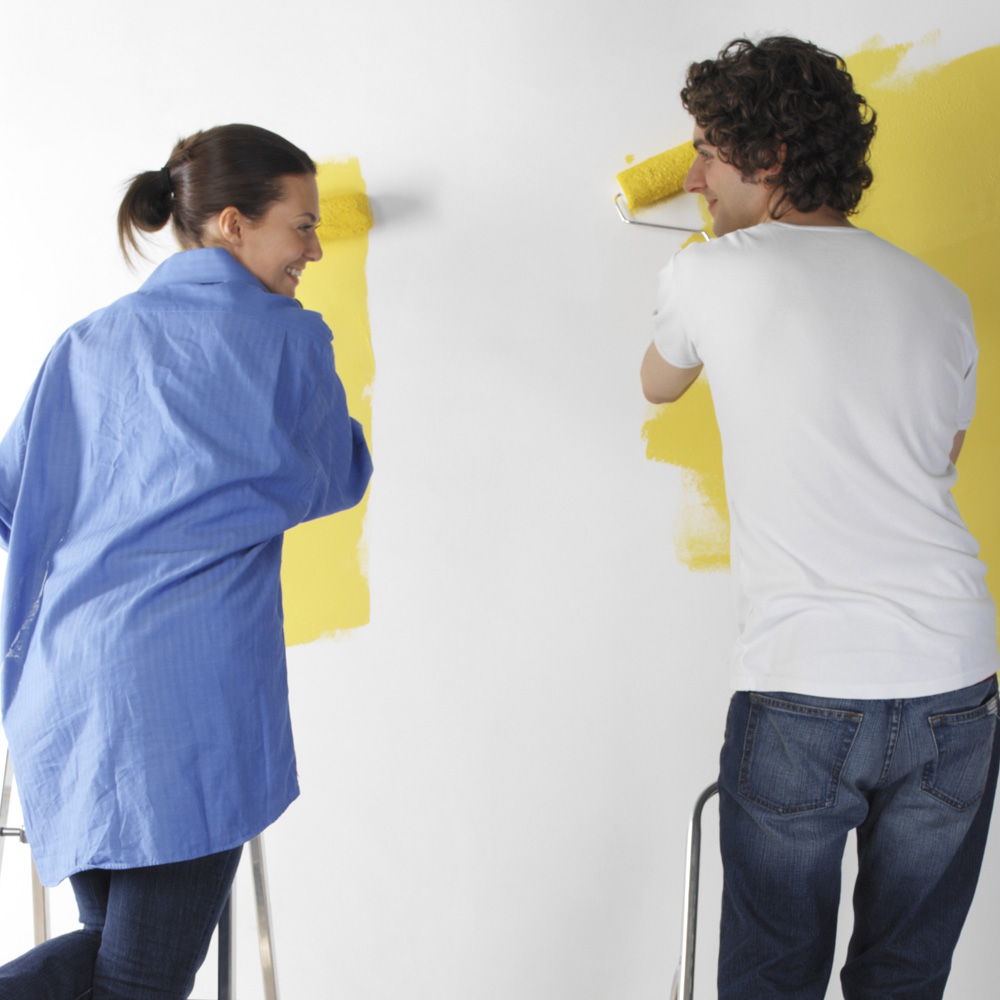 Man and woman painting a wall